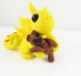 Clay yellow dragon sculpture figurine with a teddy bear